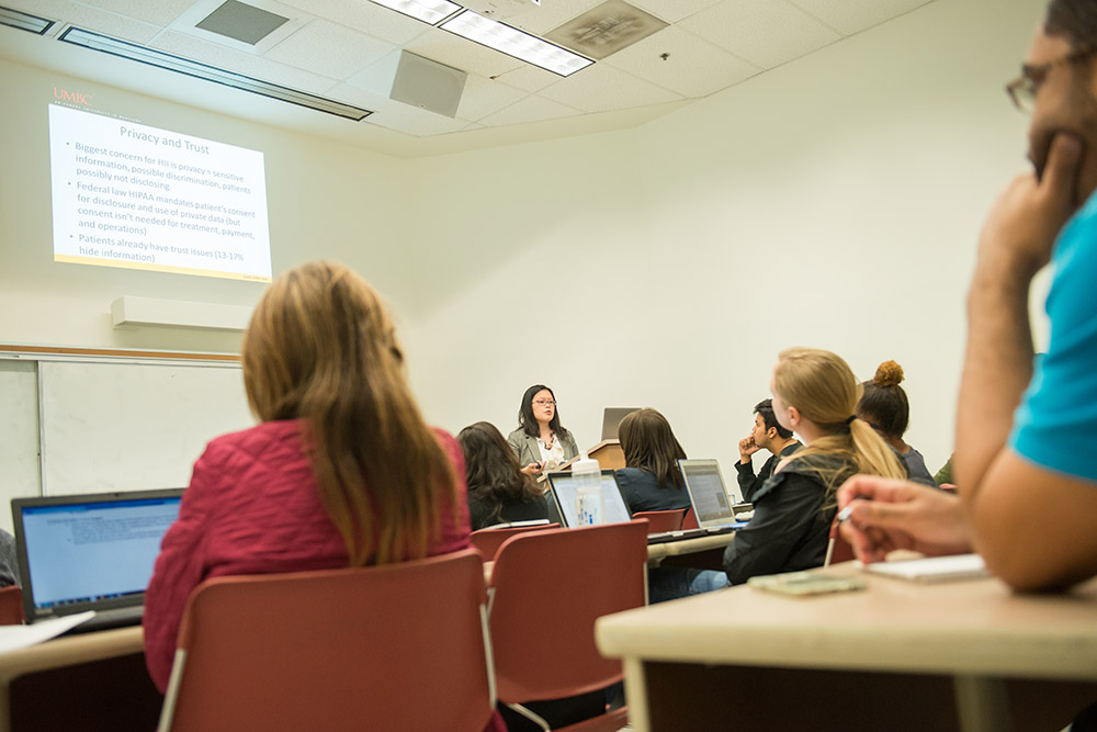 Professor speaking to active students in large classroom