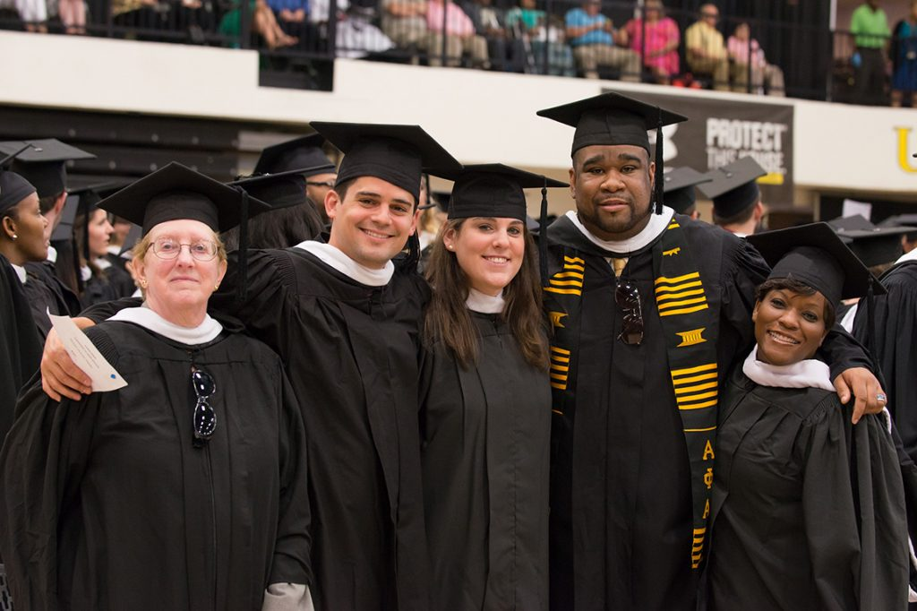 Diverse group of UMBC students in graduation attire posing at commencement