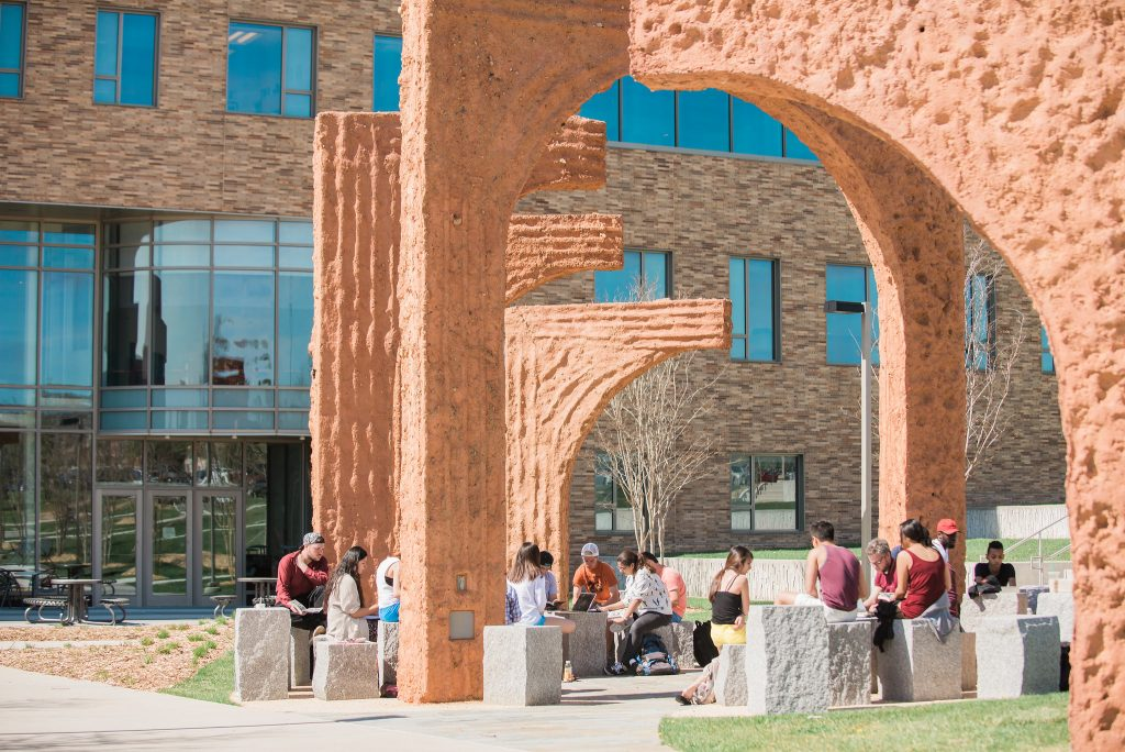 Groups of students sitting under the archway sculpture on campus