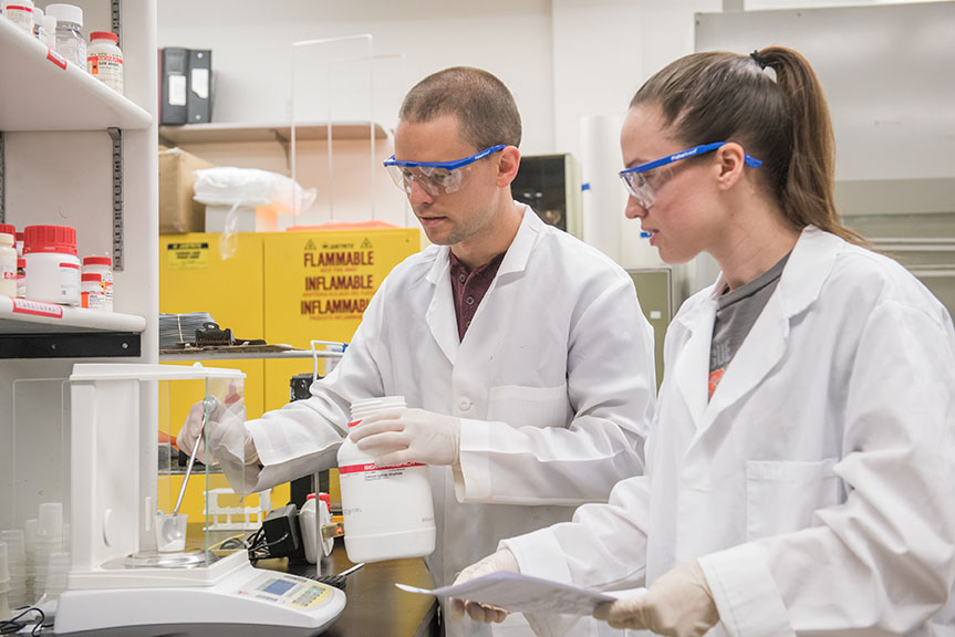 Two students working side-by-side in lab with chemicals and equipment