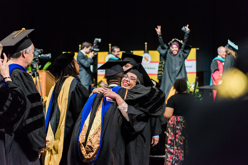 Student and professor embracing at commencement surrounded by celebrations