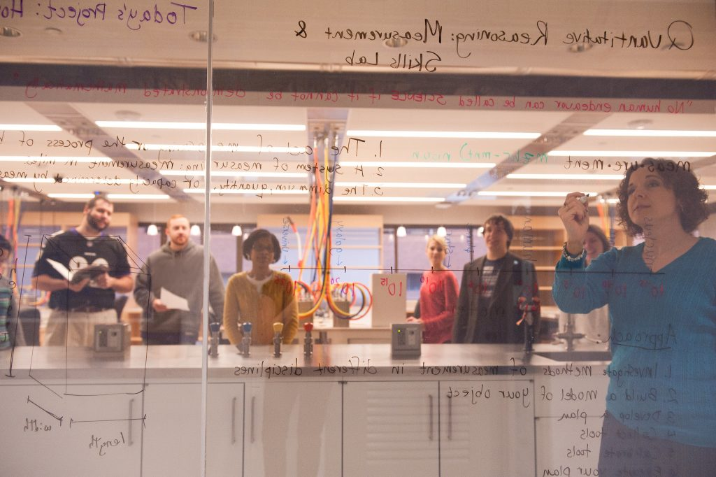 View of teacher writing through glass pane with students looking on